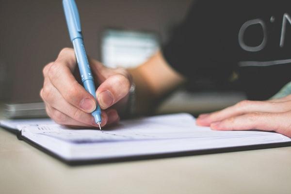 Ecrire une chanson avec un carnet et un stylo